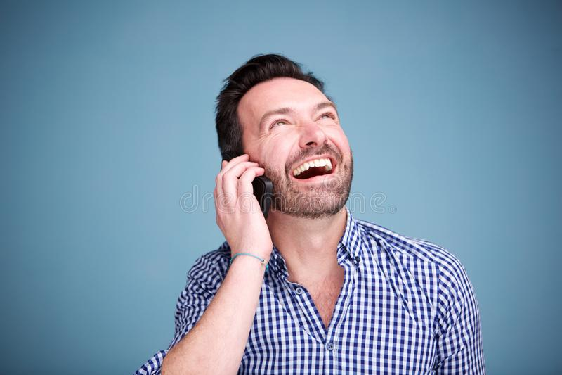 Ciérrese encima del hombre feliz que habla en el teléfono móvil y que mira para arriba fotos de archivo
