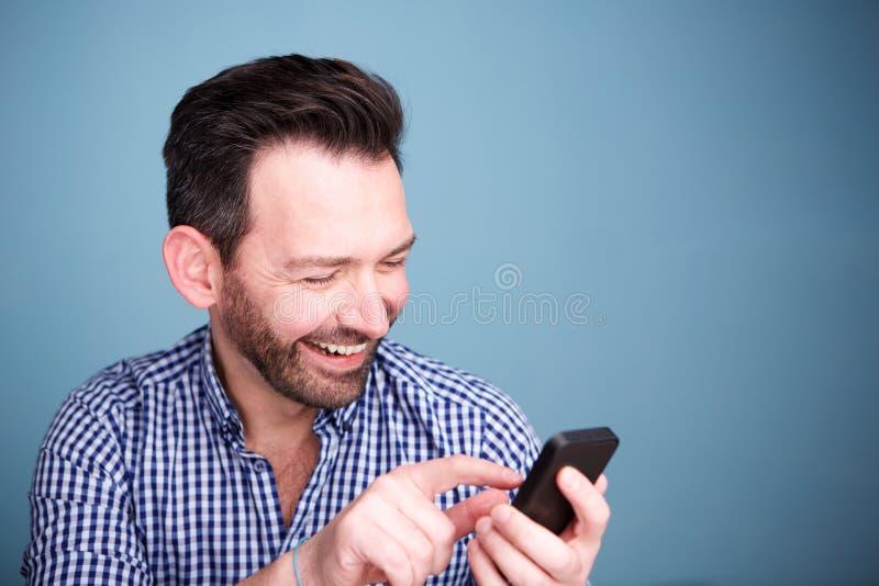 Ciérrese encima del hombre feliz que mira el mensaje de texto en el teléfono móvil fotografía de archivo