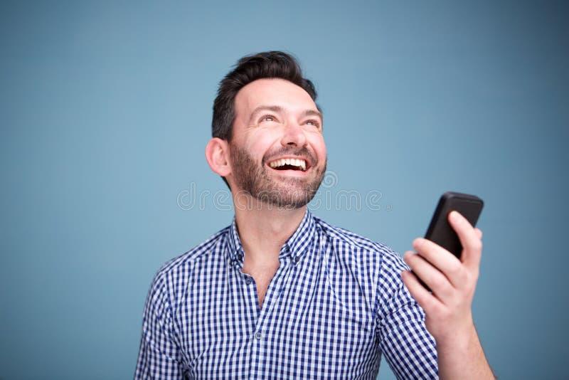 Ciérrese encima del hombre feliz que sostiene el teléfono móvil y que mira para arriba imagen de archivo libre de regalías