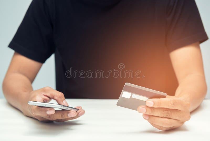 Ciérrese encima del hombre joven asiático que usa el teléfono del moblie y llevando a cabo el crédito c fotografía de archivo