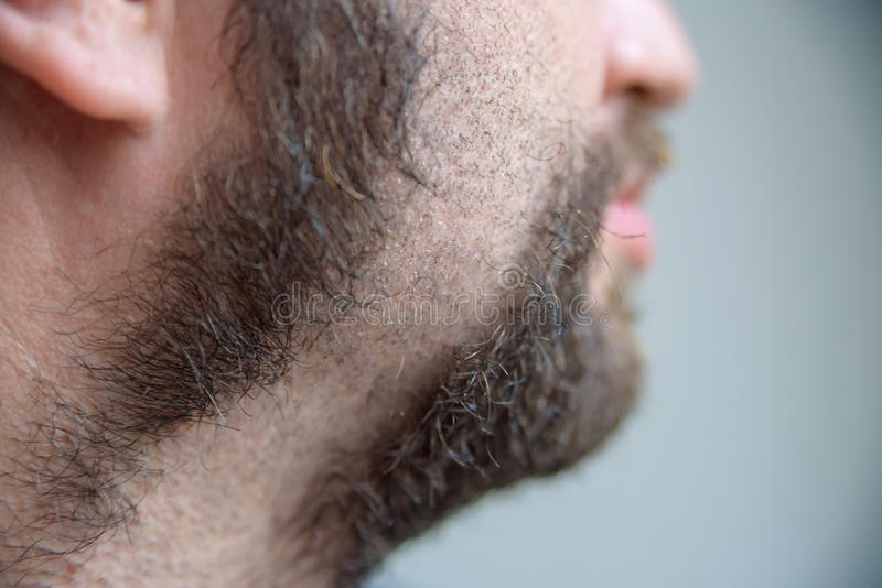 Ciérrese encima del hombre joven que afeita con la maquinilla de afeitar eléctrica foto de archivo