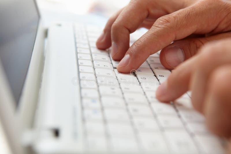 Ciérrese encima del hombre que usa el teclado de ordenador foto de archivo
