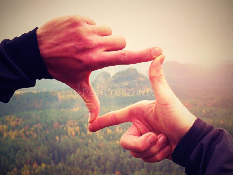 Ciérrese encima del marco masculino de los fingeres de las manos sobre paisaje foto de archivo