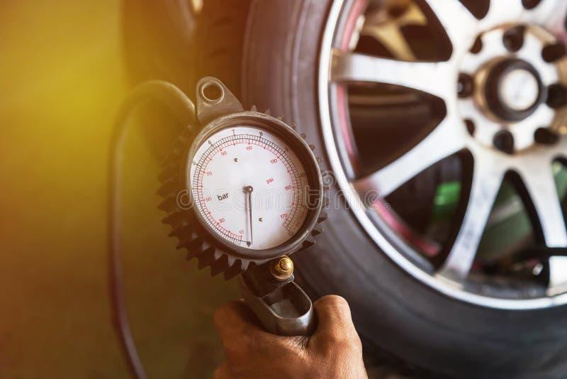 Ciérrese encima del mecánico que infla el neumático y que comprueba la presión de aire fotos de archivo
