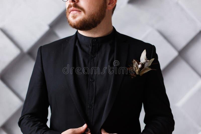 Ciérrese encima del medio retrato de la cara del jefe barbudo en traje negro y la camisa que se colocan sobre fondo geométrico gr fotografía de archivo libre de regalías