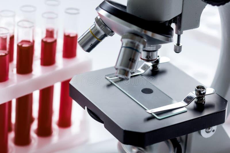 Ciérrese encima del microscopio macro con la muestra de sangre en el fondo blanco fotos de archivo