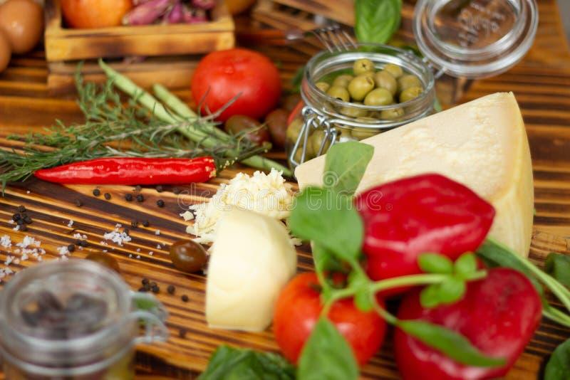 Ciérrese encima del queso, de las pimientas, de las aceitunas verdes, de los tomates y de las especias Fondo de la comida, compos foto de archivo