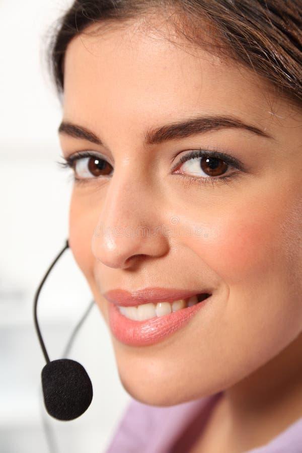 Ciérrese encima del receptor de cabeza que habla del recepcionista de sexo femenino joven foto de archivo libre de regalías