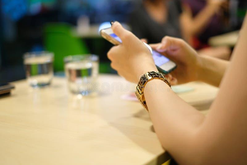 Ciérrese encima del reloj de lujo con la muchacha que practica surf la red social en el teléfono elegante imagenes de archivo