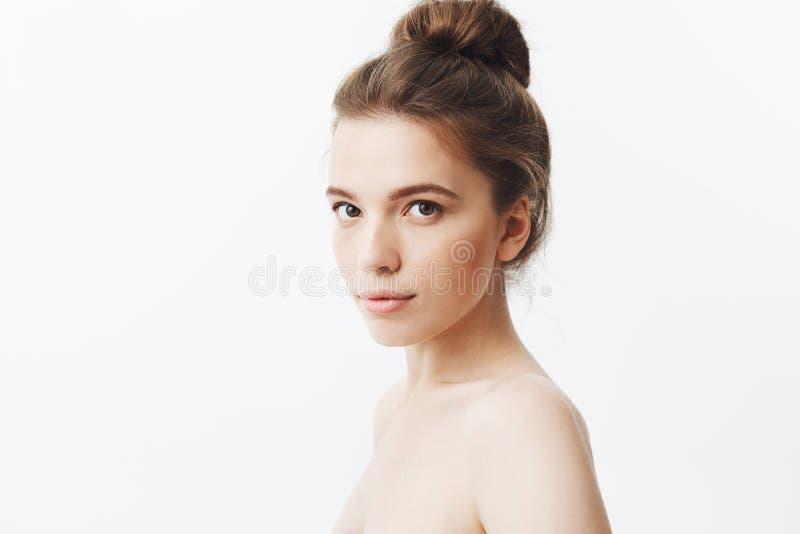 Ciérrese encima del retrato aislado de la mujer flaca joven hermosa relajada con el pelo oscuro largo en peinado del bollo, plant fotografía de archivo