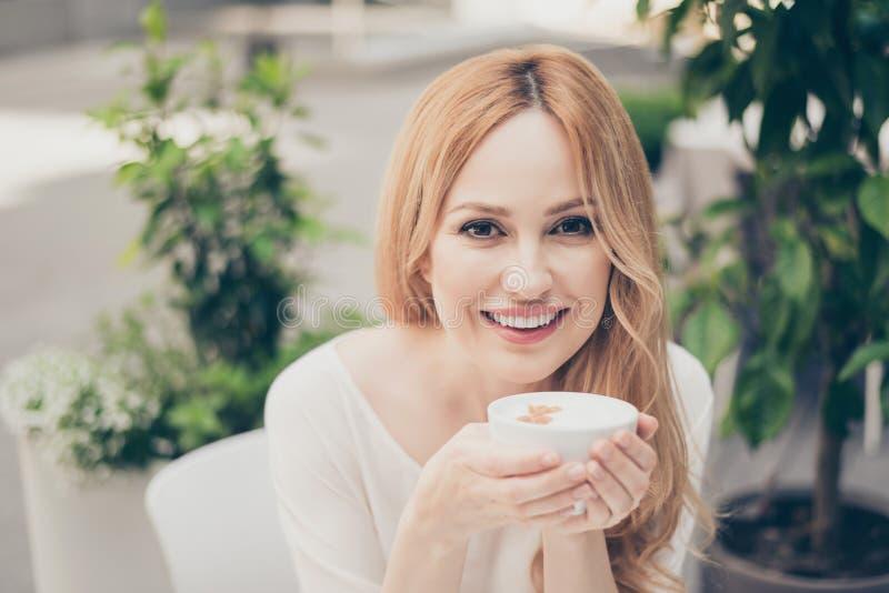 Ciérrese encima del retrato al aire libre de la ciudad del sittin sonriente caucásico de la mujer imágenes de archivo libres de regalías