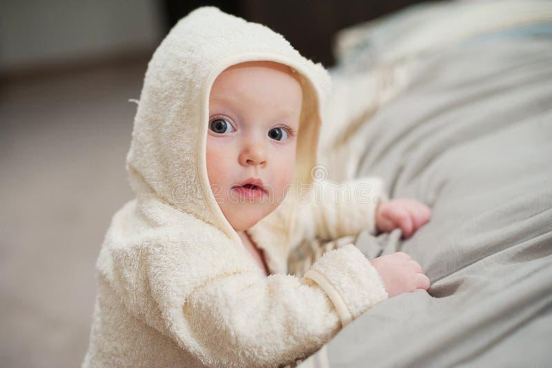 Ciérrese encima del retrato del bebé divertido lindo en albornoz fotografía de archivo libre de regalías