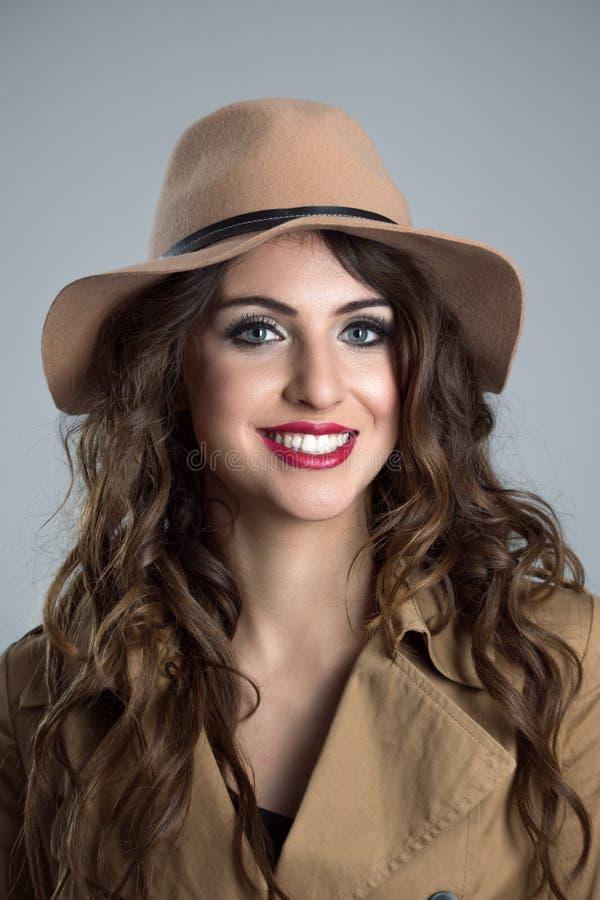 Ciérrese encima del retrato cambiante del sombrero que lleva de la mujer joven y de la sonrisa beige de la capa imagen de archivo libre de regalías