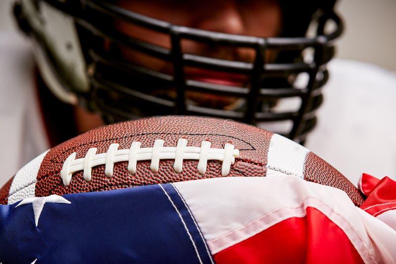 Ciérrese encima del retrato croped del futbolista en casco con la bola y de la bandera americana en un fondo blanco imagen de archivo libre de regalías