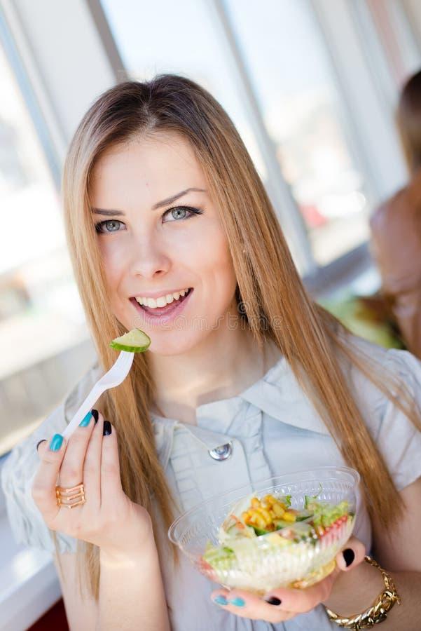 Ciérrese encima del retrato de comer a la mujer joven hermosa de la ensalada deliciosa que se divierte en sonrisa feliz del resta foto de archivo libre de regalías