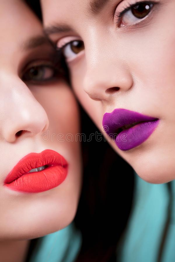 Ciérrese encima del retrato de dos mujeres hermosas con maquillaje brillante, con rojo y púrpura del penique, los labios rosados  imagenes de archivo