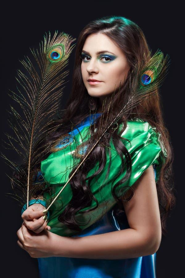 Ciérrese encima del retrato de la belleza de la muchacha hermosa con la pluma del pavo real Plumas creativas del peafowl del maqu fotos de archivo
