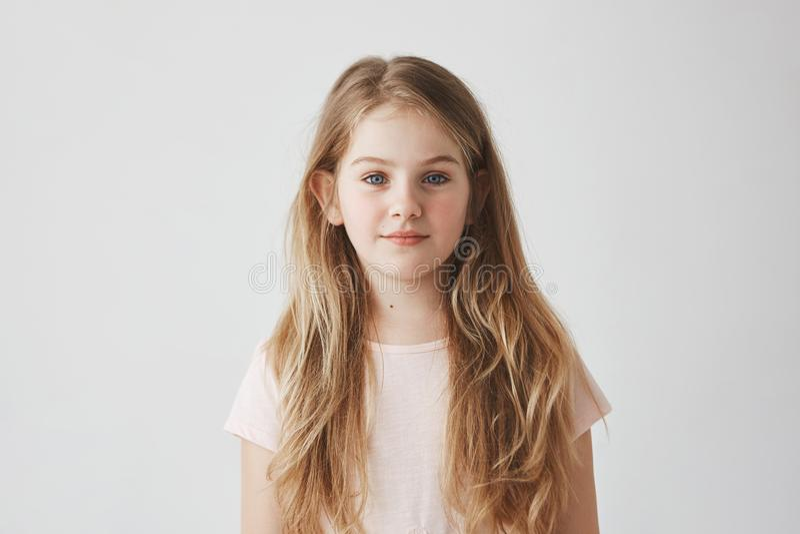 Ciérrese encima del retrato de la chica joven apuesta con el pelo rubio en vestido rosado, mirando in camera con la expresión tra fotografía de archivo