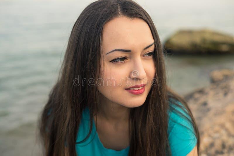 Ciérrese encima del retrato de la chica joven hermosa en la playa imagenes de archivo