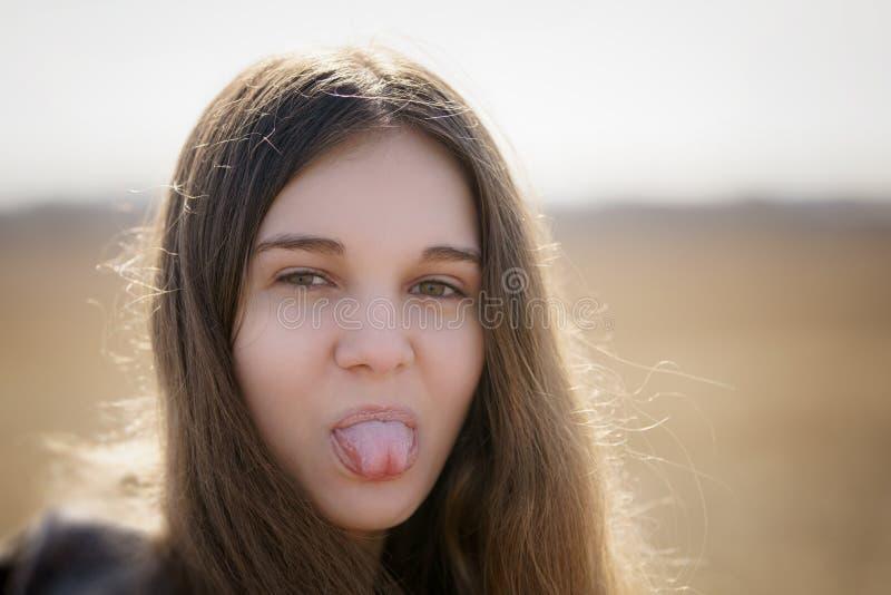 Ciérrese encima del retrato de la chica joven que muestra la lengua imagenes de archivo