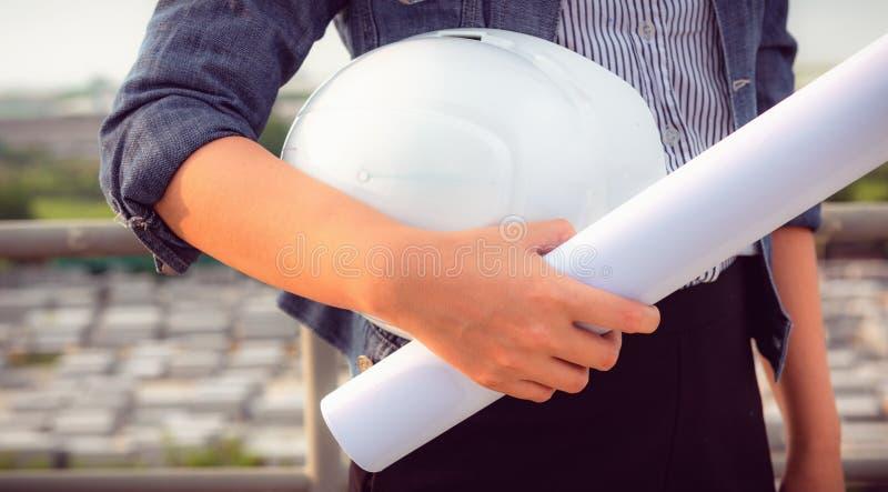 Ciérrese encima del retrato de la mano de la mujer del ingeniero civil que sostiene el casco de protección a foto de archivo libre de regalías