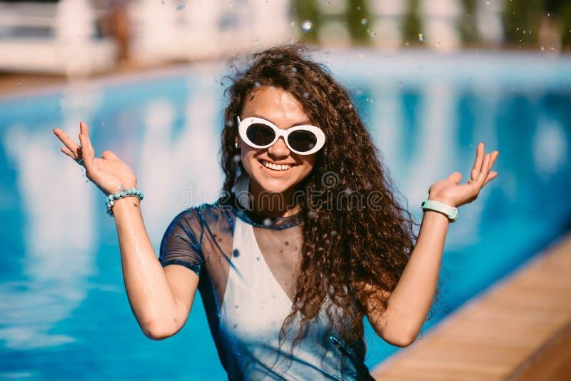 Ciérrese encima del retrato de la moda de la mujer morena sonriente sensual de la belleza que presenta en piscina, relajándose di imagen de archivo