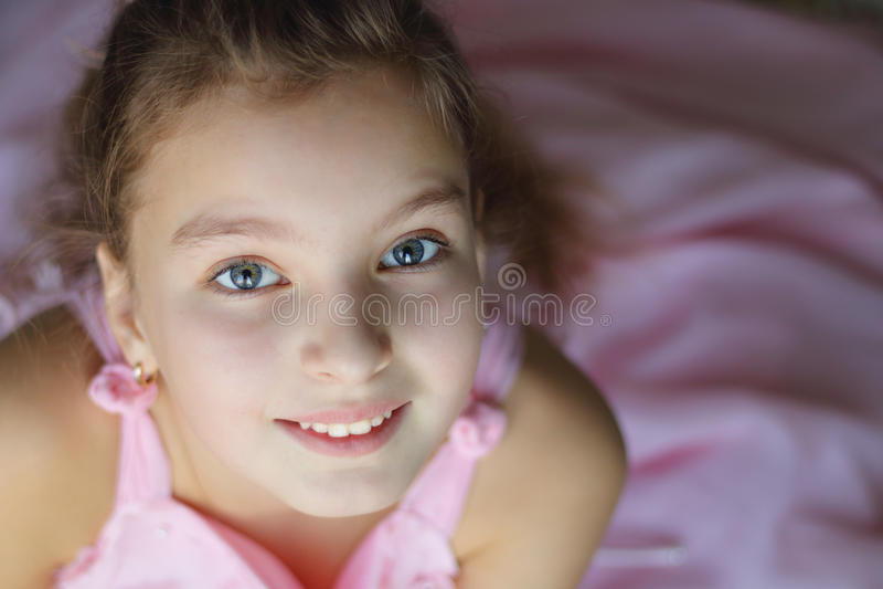 Ciérrese encima del retrato de la muchacha adolescente hermosa en vestido rosado entusiasta con una sonrisa que mira la cámara imagen de archivo