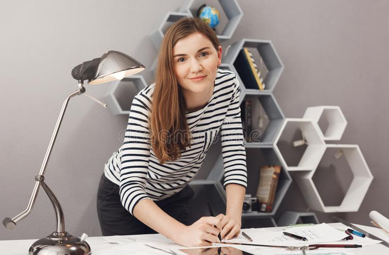 Ciérrese encima del retrato de la muchacha alegre encantadora joven del estudiante del ingeniero que coloca la tabla cercana, lle fotografía de archivo libre de regalías