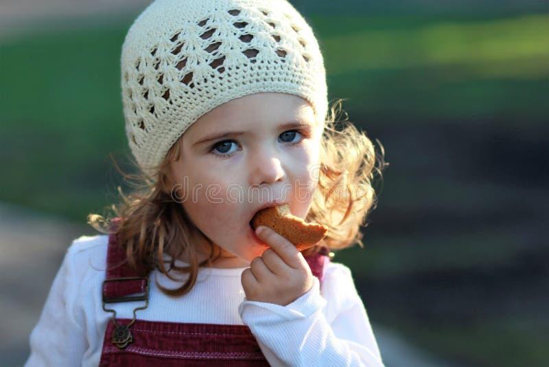Ciérrese encima del retrato de la muchacha de un año linda en un sombrero hecho punto blanco que come la galleta en un paseo en e imagenes de archivo