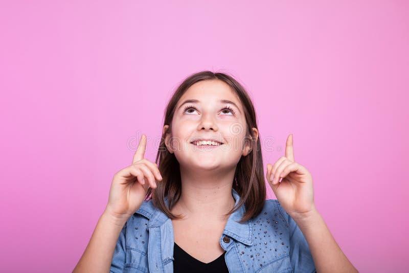 Ciérrese encima del retrato de la muchacha feliz poiting para arriba fotografía de archivo