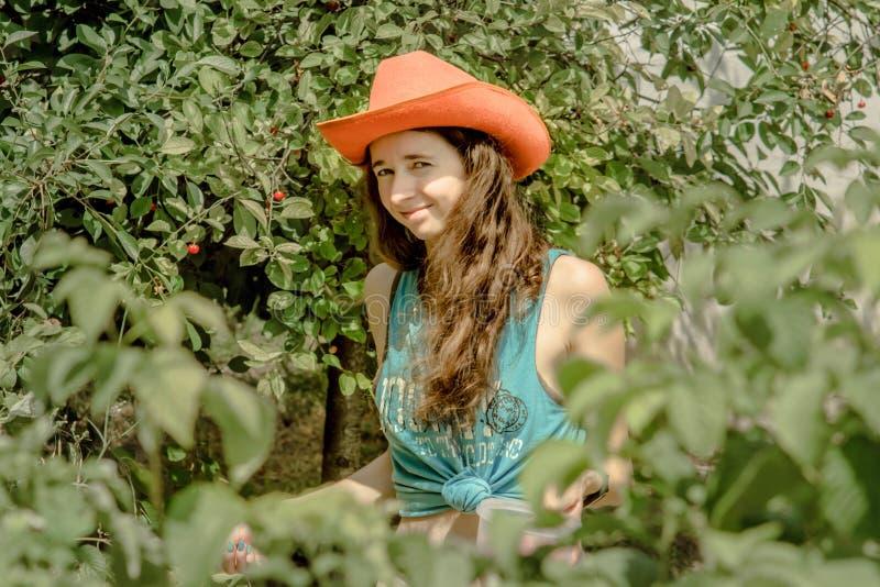 Ciérrese encima del retrato de la muchacha hermosa rizada con las cerezas anaranjadas de la cosecha del sombrero de vaquero imagenes de archivo