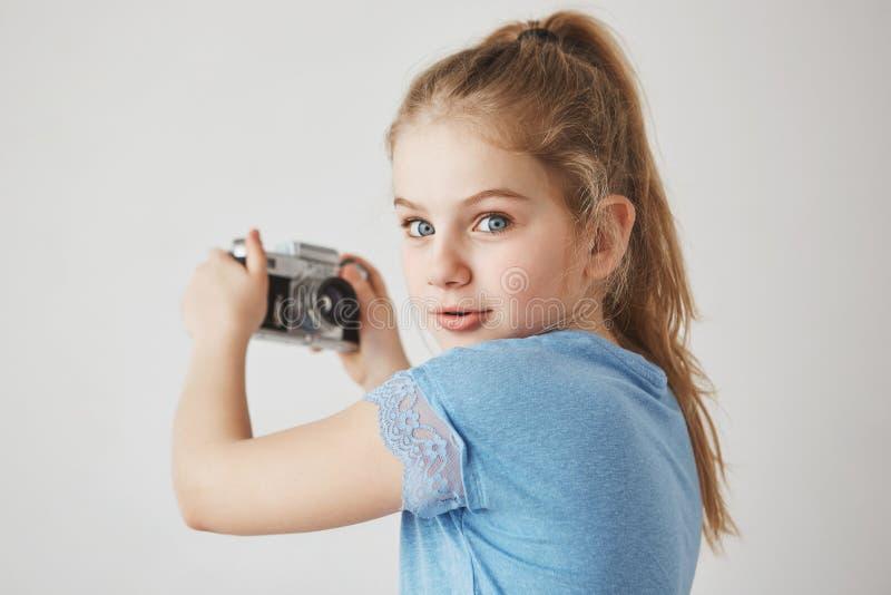 Ciérrese encima del retrato de la muchacha linda alegre con el pelo rubio y los ojos azules, mirando in camera con la expresión i foto de archivo libre de regalías