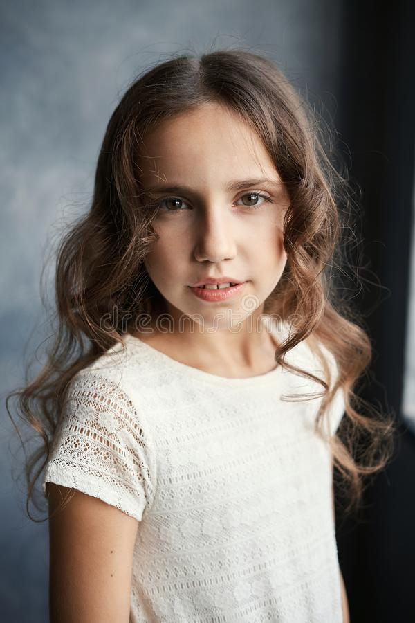 Ciérrese encima del retrato de la muchacha morena hermosa joven en la camisa blanca que mira la cámara fotografía de archivo libre de regalías