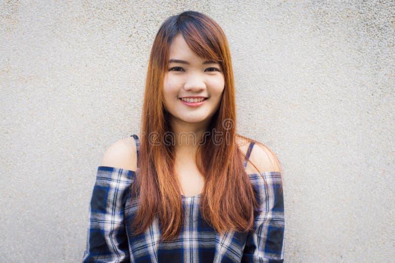 Ciérrese encima del retrato de la mujer asiática joven feliz que sonríe y que guiña contra el muro de cemento gris Estilo del col foto de archivo