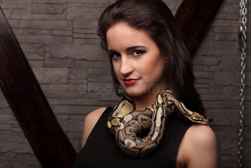 Ciérrese encima del retrato de la mujer atractiva con la serpiente en vestido negro que sonríe, labios rojos foto de archivo libre de regalías