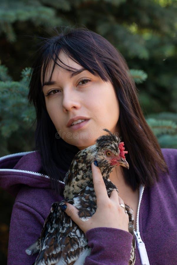 Ciérrese encima del retrato de la mujer con un pollo abigarrado en su h fotografía de archivo