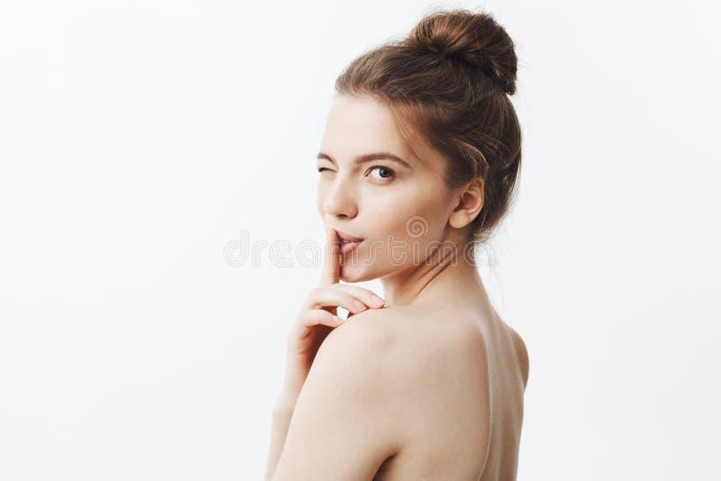 Ciérrese encima del retrato de la mujer europea joven hermosa encantadora con el pelo largo oscuro en peinado del bollo y piel de fotos de archivo