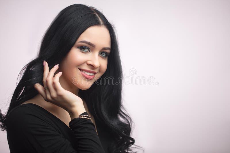 Ciérrese encima del retrato de la mujer joven hermosa feliz con el pelo negro largo imagenes de archivo