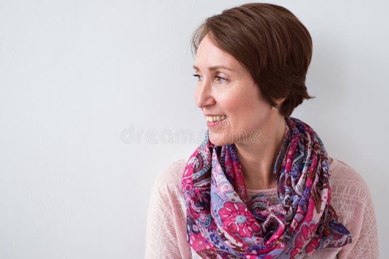 Ciérrese encima del retrato de la mujer morena sonriente con la bufanda colorida foto de archivo libre de regalías