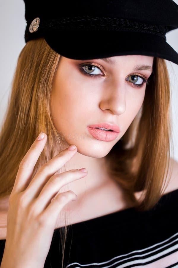 Ciérrese encima del retrato de la mujer rubia atractiva con el profesional componen, en un casquillo La muchacha mira la cámara fotografía de archivo libre de regalías