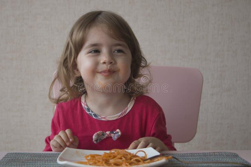 Ciérrese encima del retrato de la niña adorable que come los espaguetis y la sonrisa foto de archivo libre de regalías