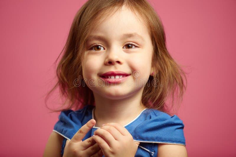 Ciérrese encima del retrato de la niña con los ojos marrones hermosos en rosa aislado imagenes de archivo