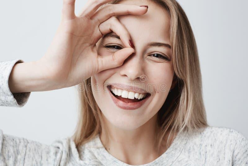 Ciérrese encima del retrato de la sonrisa femenina caucásica rubia alegre hermosa, demostrando los dientes blancos, mirando la cá fotos de archivo libres de regalías