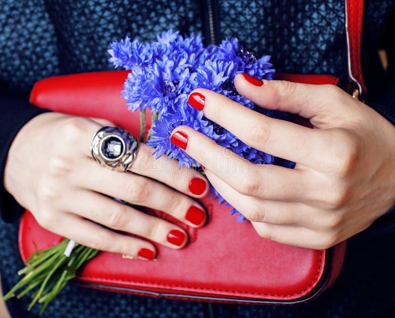 Ciérrese encima del retrato de las manos manicured las muchachas que sostienen el pequeño ramo rojo lindo del bolso y del aciano, fotografía de archivo libre de regalías
