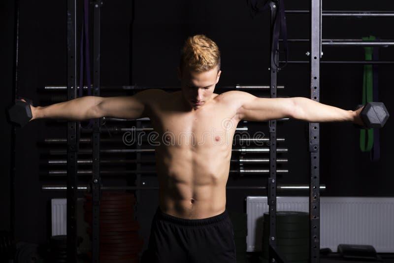 Ciérrese encima del retrato de los pesos de elevación de un hombre joven del ajuste en gimnasio en fondo oscuro foto de archivo libre de regalías