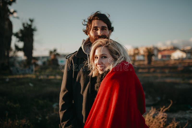 Ciérrese encima del retrato de pares alternativos jovenes, al aire libre, en la puesta del sol, mientras que miran la sonrisa de  fotografía de archivo libre de regalías