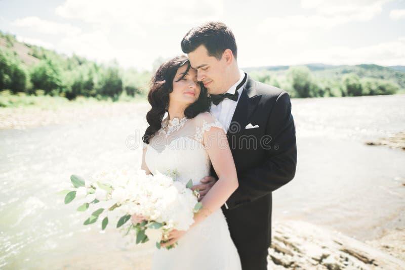 Ciérrese encima del retrato de pares contra el río y árboles verdes Mujer joven hermosa que besa al hombre hermoso al aire libre foto de archivo