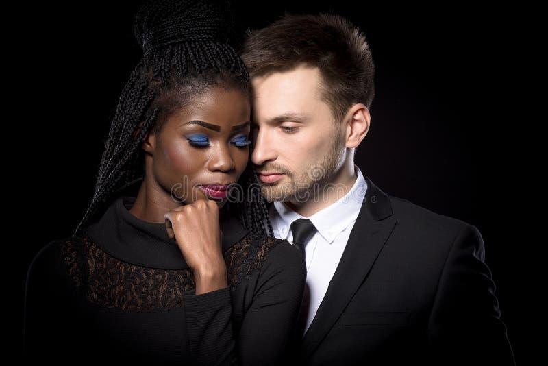 Ciérrese encima del retrato de pares multi-étnicos románticos en fondo negro fotografía de archivo libre de regalías