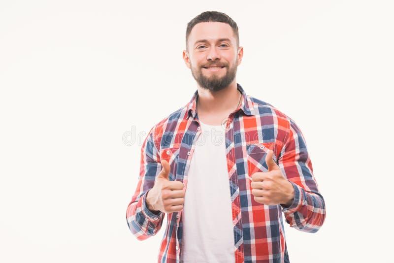 Ciérrese encima del retrato de un hombre casual feliz que muestra los pulgares encima del gesto sobre el fondo blanco imagenes de archivo