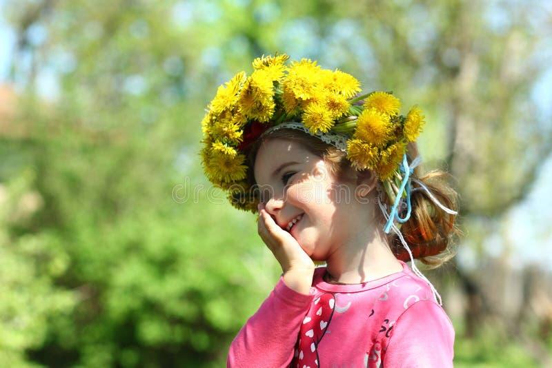 Ciérrese encima del retrato de un lindo riendo dos años de la muchacha que lleva una guirnalda del diente de león imagen de archivo